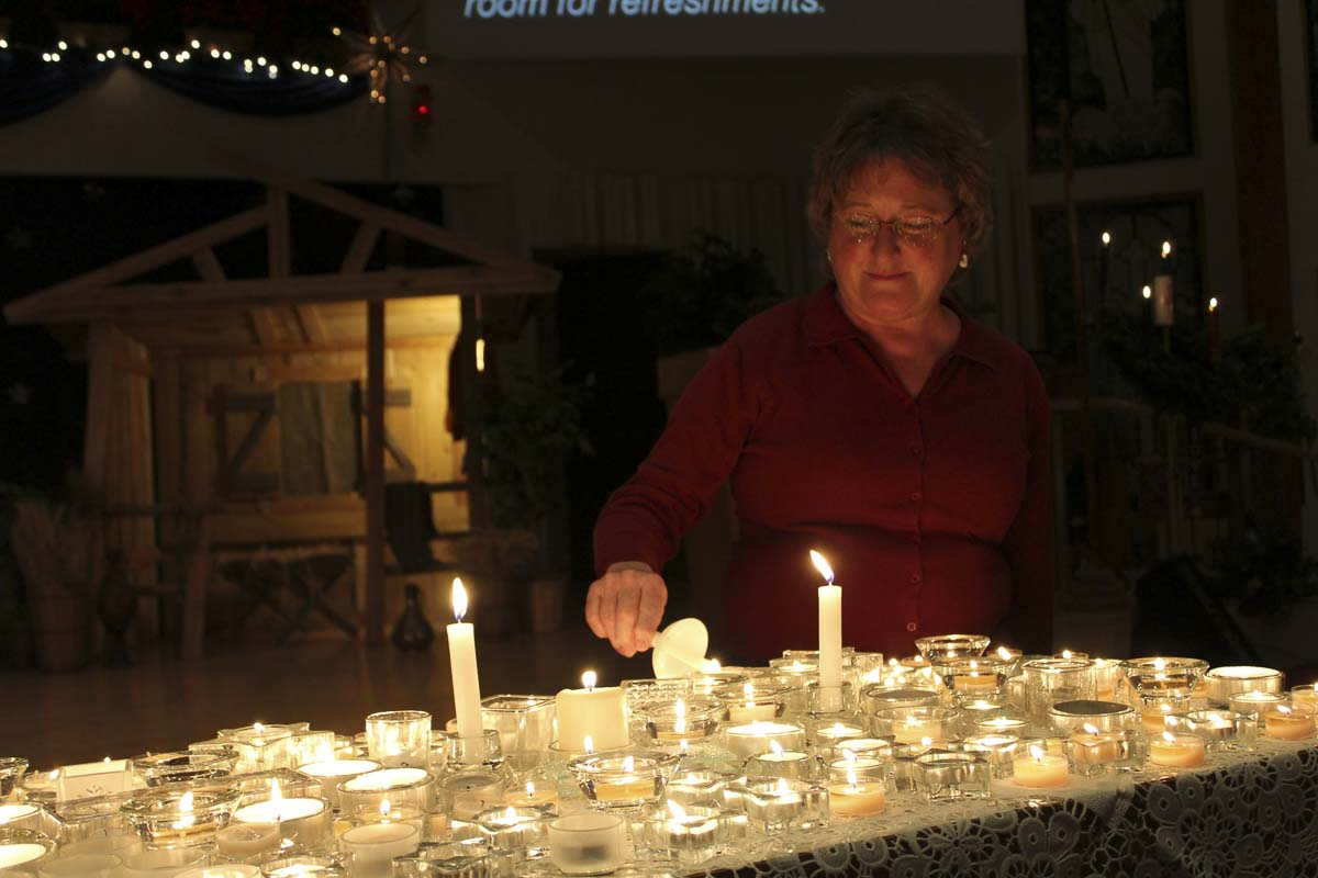Jan Allen lights a candle at a previous Longest Night Service. Photo courtesy of Diane Stevens
