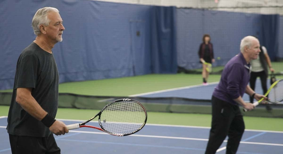 Jim Boyer (left) plays doubles tennis during a class night at the VTC. Boyer is one of 16 people in the U.S. to survive as a result of an experimental treatment for brain cancer. Photo by Jacob Granneman