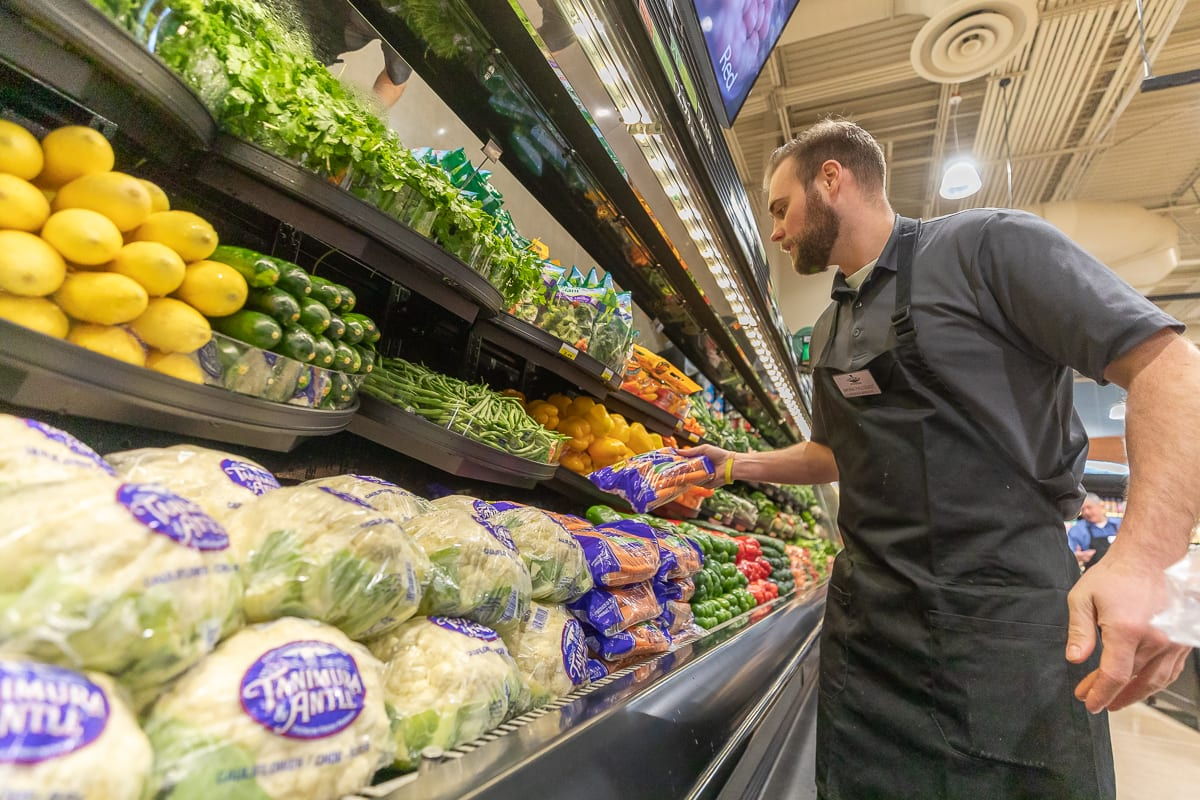 Rosauers Supermarket Produce Manager Bryan Fallquist puts the final touches on his display ahead of the Ridgefield location grand opening on Saturday. Photo by Mike Schultz