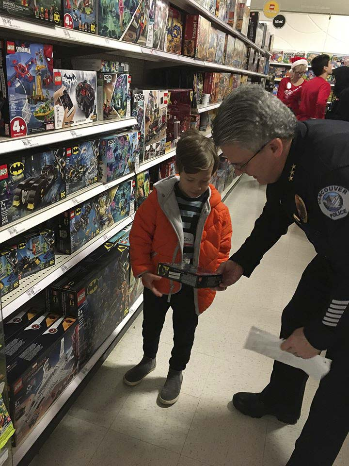 Vancouver Police Chief James McElvain assists a youngster with his toy selection at the Vancouver Police Officer's Guild Shop With a Cop event Saturday at Target. Photo courtesy of Vancouver Police Department