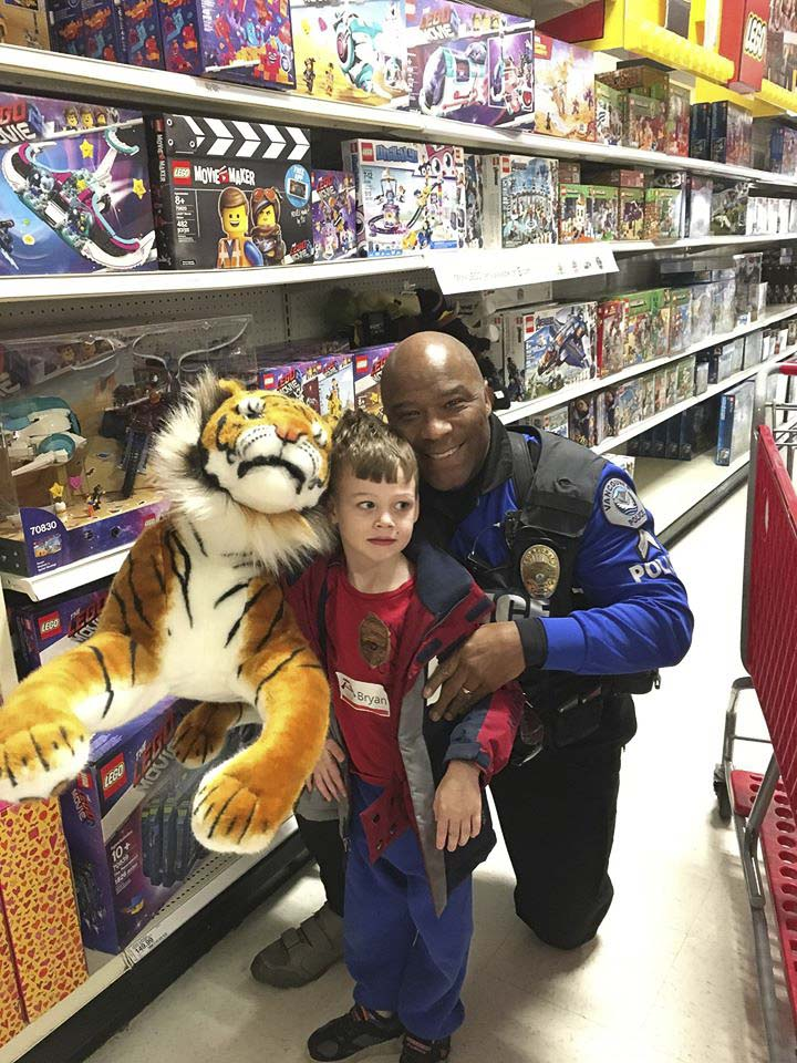 Cpl. Rey Reynolds and this youngster found a furry friend at Saturday's Shop With a Cop event, organized by the Vancouver Police Officer's Guild and Nautilus, Inc. Photo courtesy of Vancouver Police Department