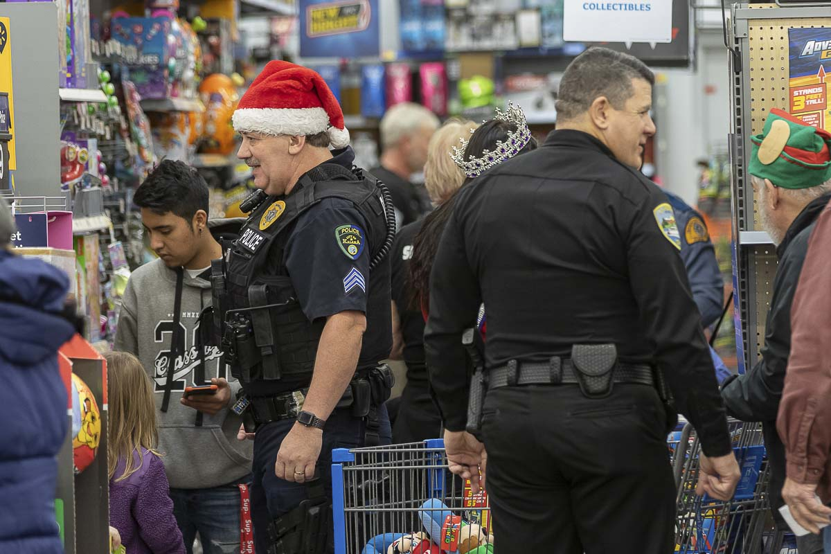 Officers from Kalama and La Center shop with children at the ninth annual Shop with a Cop. More than 200 children received gifts this year. Photo by Mike Schultz