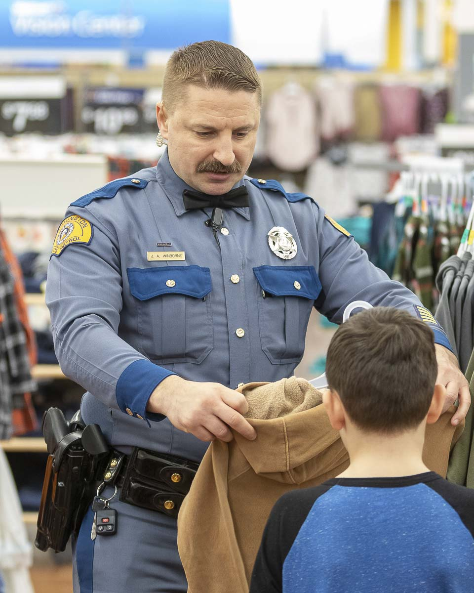 Washington State Patrol Trooper Josh Winborne shops during Shop with a Cop with Lucas. Photo by Mike Schultz