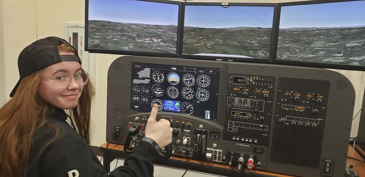 Battle Ground High School junior Brooke Kirby sits at the controls of a flight simulator. Photo courtesy of Battle Ground Public Schools