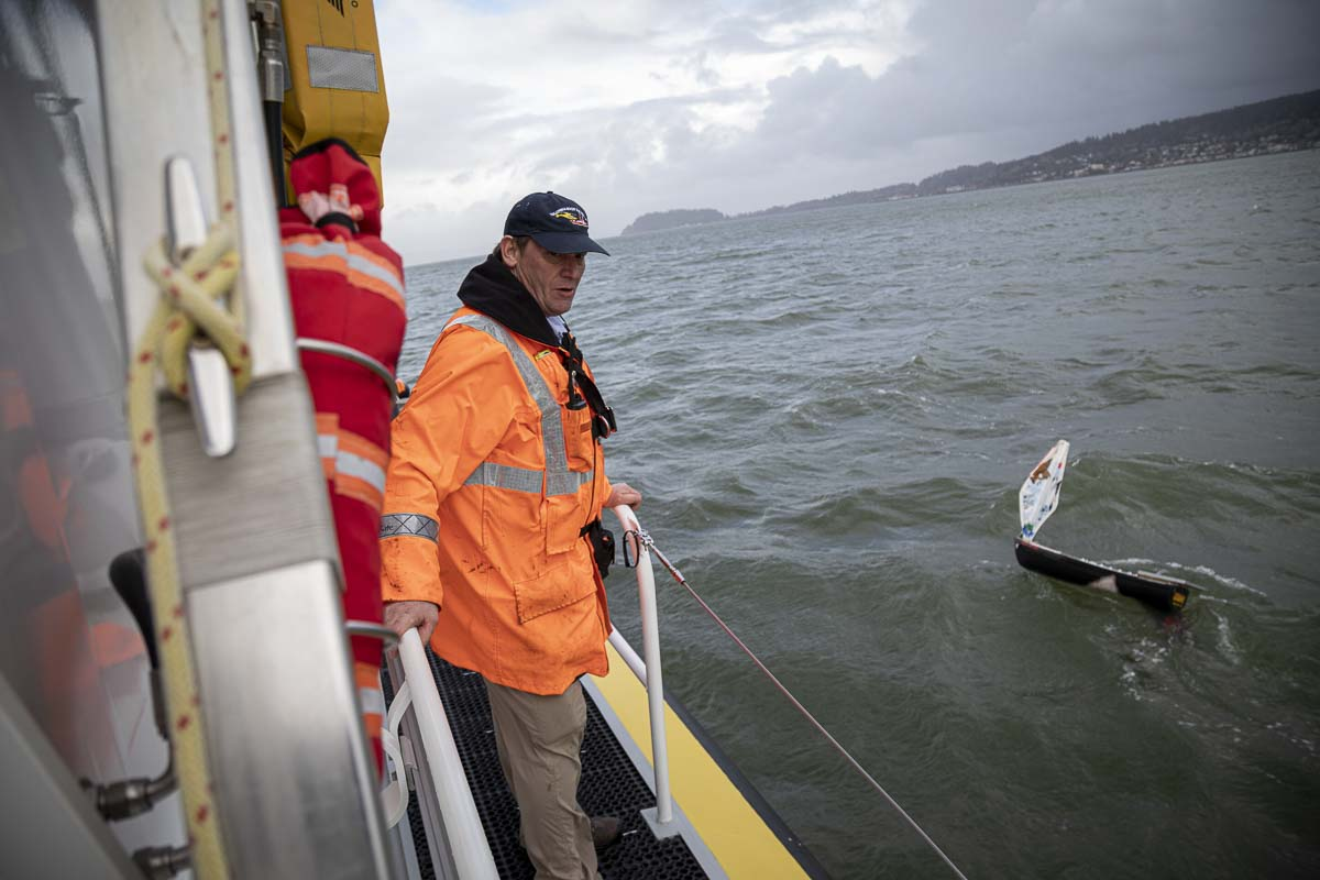 "Columbia River Bar Pilot Captain Dan Jordan works with his crew aboard the pilot boat ""Astoria"" to retrieve a mini-boat after its sea trial in the Columbia River. Photo by Jacob Granneman"