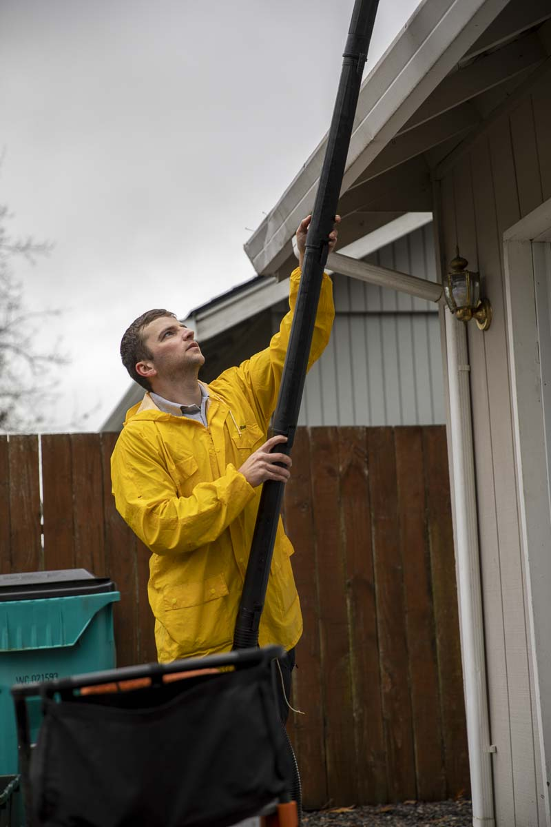 Dee Giuchici cleans the gutters for Vancouver Resident Nancy Montgomery, who is retired and needed the service. Photo by Jacob Granneman
