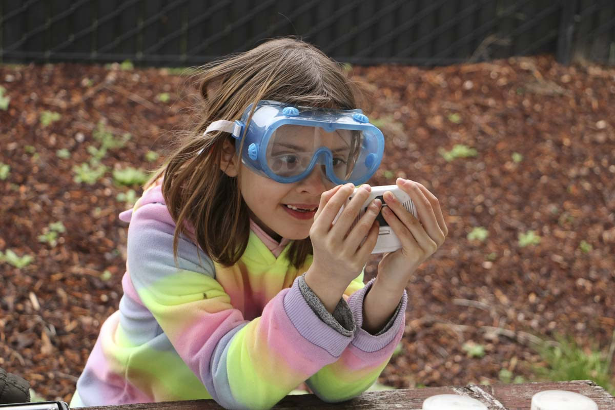 A third grader at Maple Grove Primary School wears protective goggles while studying a water sample. Photo courtesy of Battle Ground Public Schools