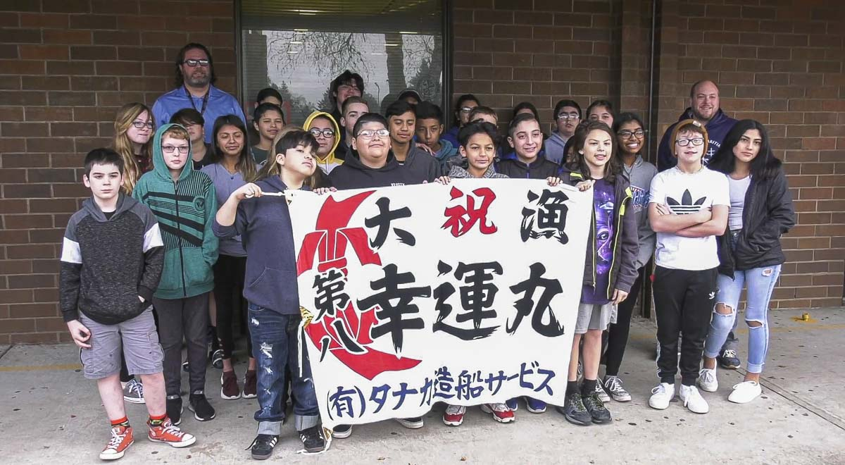 Student's from Joe Boken's science class at Wy'east Middle School in Vancouver pose with a Japanese poster after completing their mini-boat bound for Japan. Photo courtesy of Evergreen Public Schools
