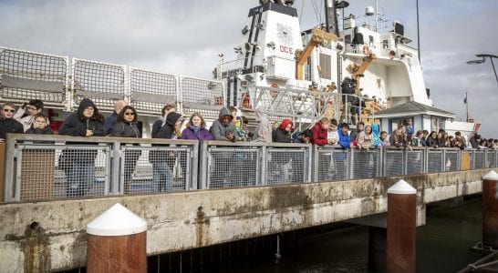 """Students from Wy'east Middle School in Vancouver line the dock in Astoria, Ore. waiting for the launch of their mini-boat, """"Liberty."""" Photo by Jacob Granneman"""