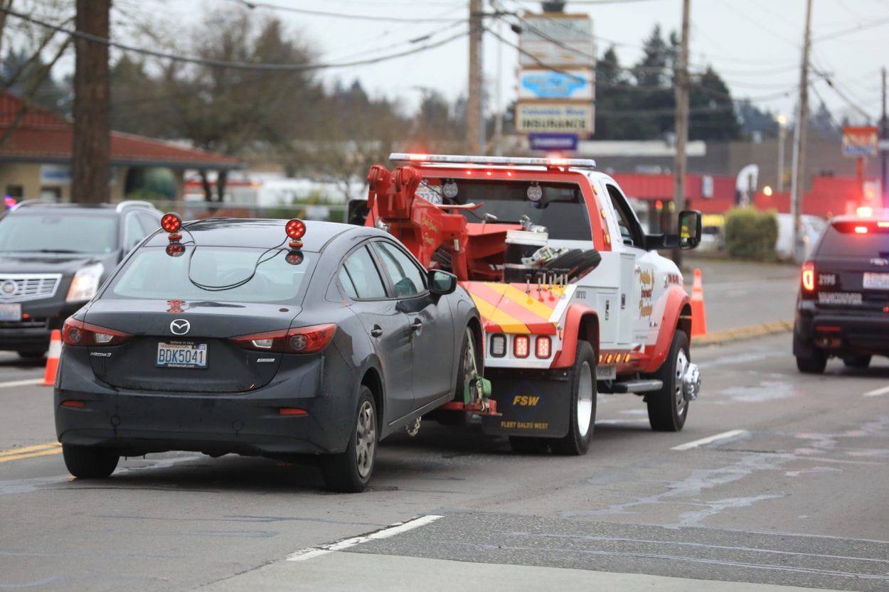 A vehicle is towed past the scene of a deadly shooting in Vancouver. Photo by Mike Schultz