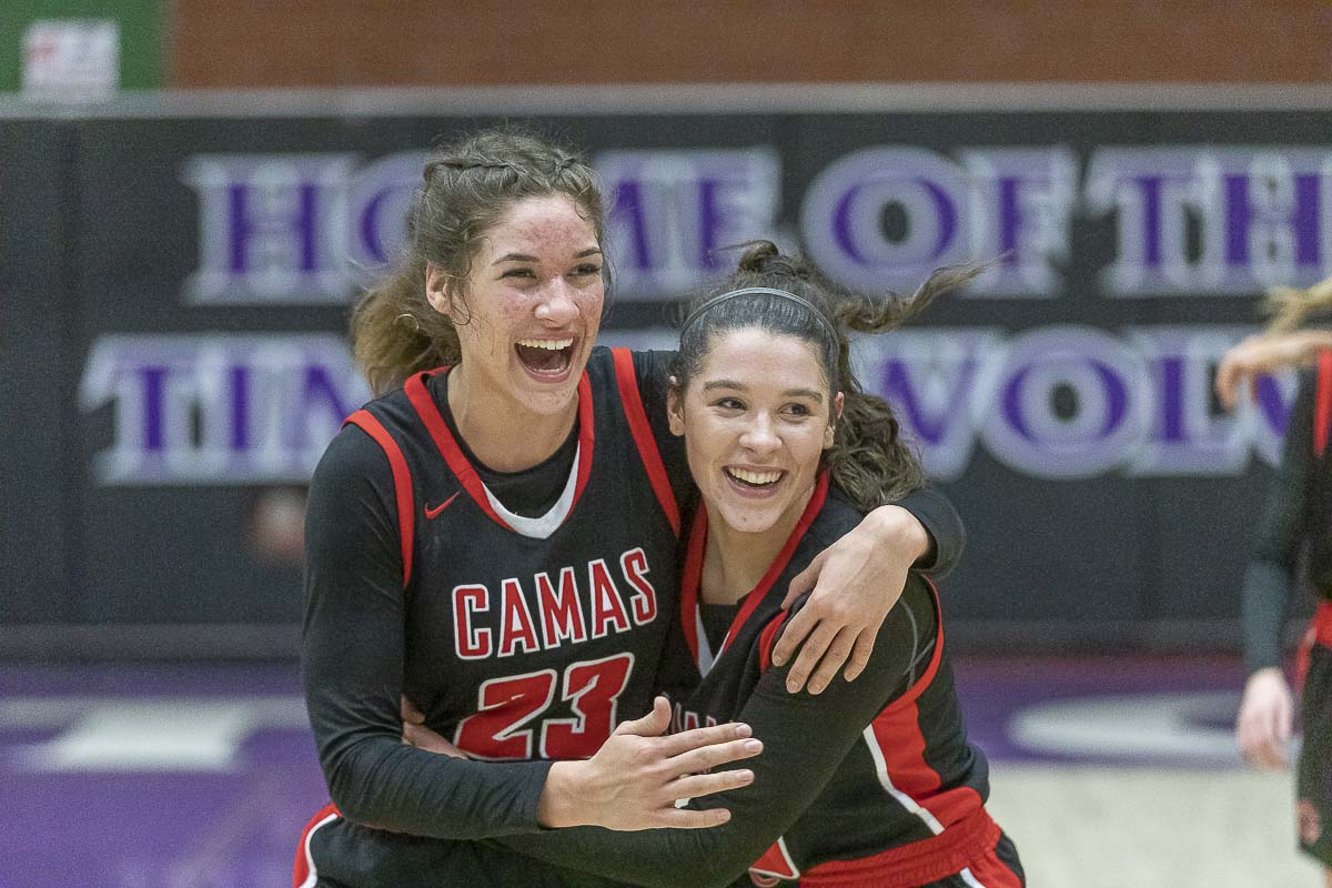 Jalena Carlisle (23) and Katelyn Forner celebrate Camas' 50-32 win over rival Skyview on Tuesday to clinch a berth to state. Photo by Mike Schultz