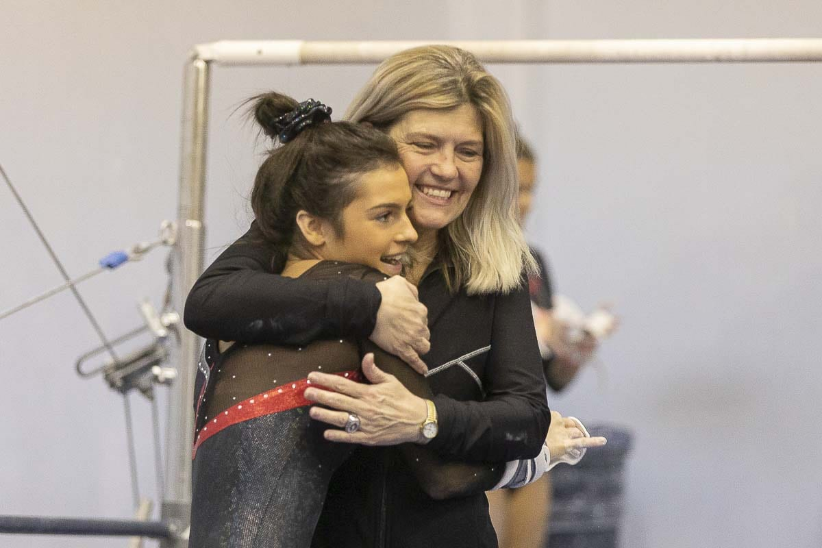 Camas coach Carol Willson gives Annika Affleck a hug after a recent gymnastics meet. Willson said the key is that she and her assistants show love to the athletes first. The sport comes second. Photo by Mike Schultz
