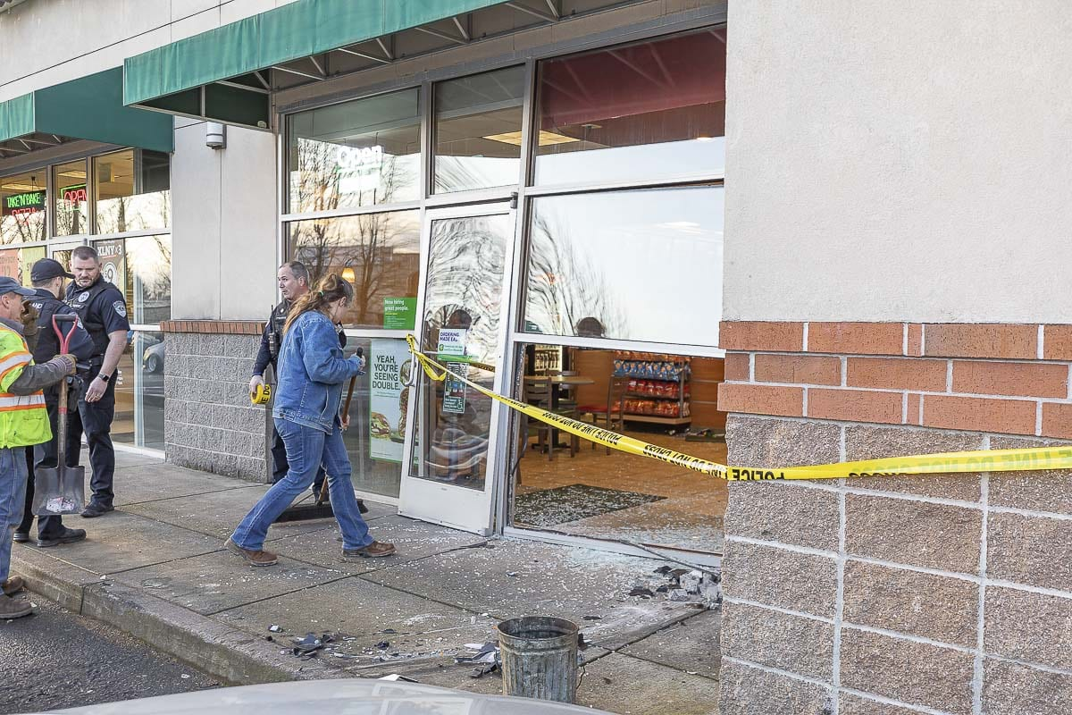 An employee begins cleaning up the mess after a car slammed into the front of a Subway restaurant in Woodland on Sunday. Photo by Mike Schultz