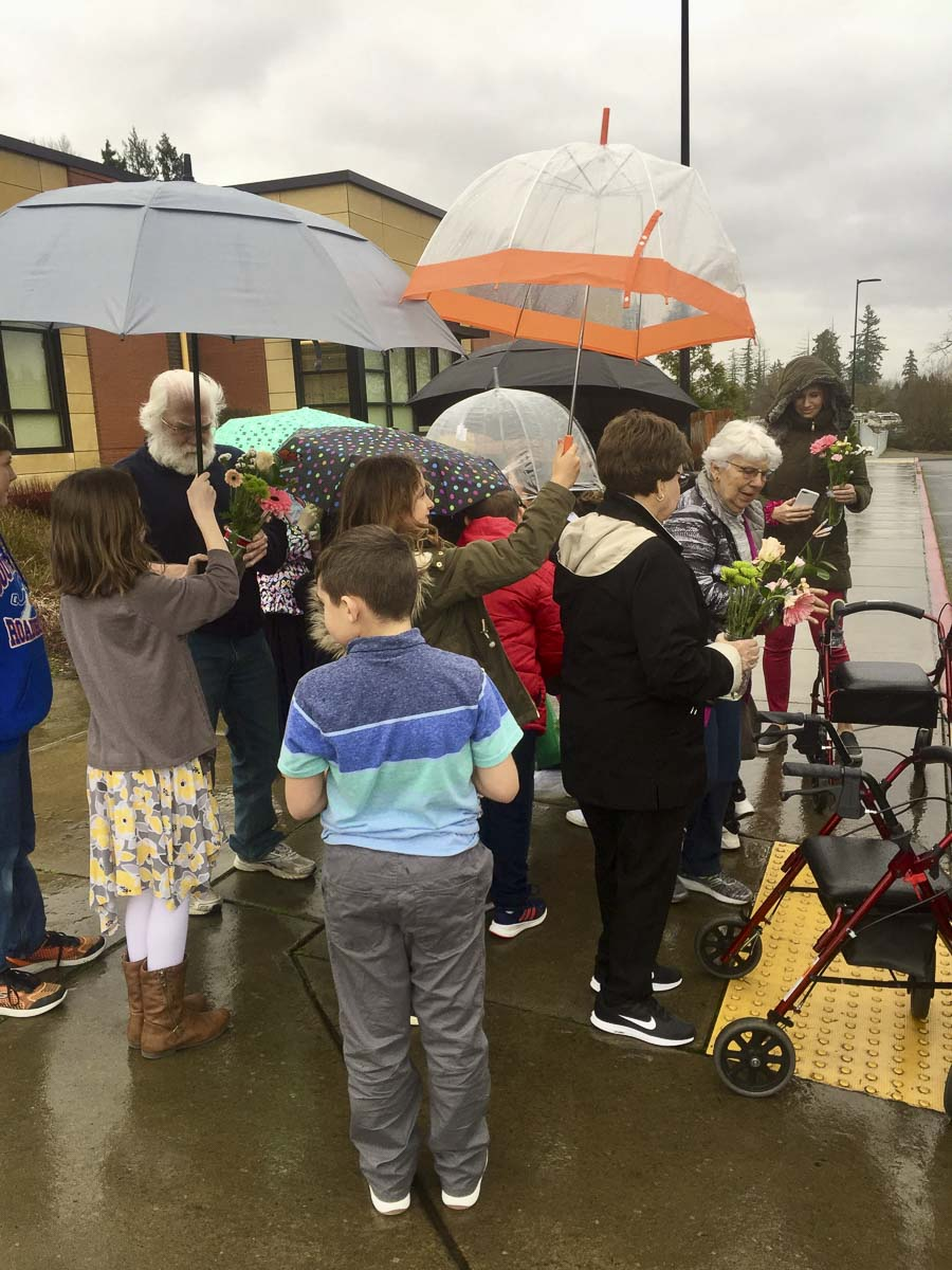 After a classroom visit, South Ridge Elementary students shield their friends from the rain as they wait to board buses to return to Highgate. Photo courtesy of Ridgefield Public Schools