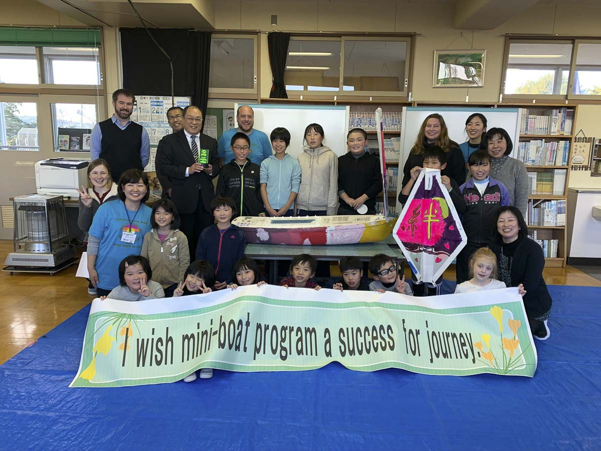 The class of Tanesashi Elementary School in Japan is seen here with their mini-boat and CRMM Education Director, Nate Sandel. Photo courtesy of CRMM