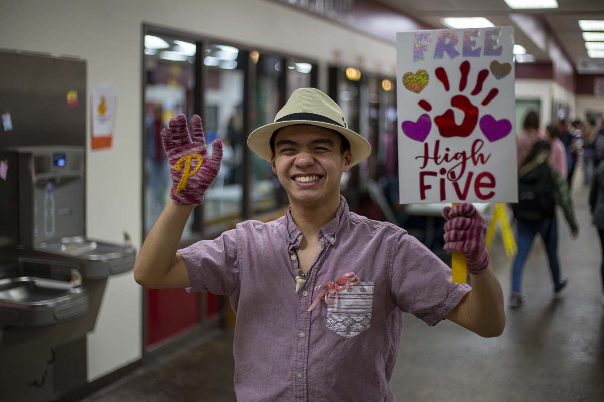 "PHS student Seth Le, better known as ""The High Five Guy,"" walks around school giving free high fives to anyone and everyone as part of Inspire Week 2020. Photo by Jacob Granneman"