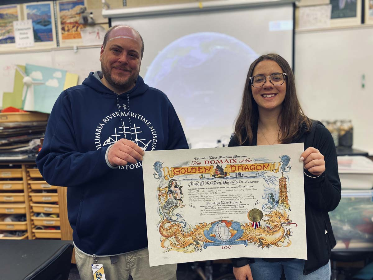 CRMM Educational Director Nate Sandel (left) holds up a Domain of the Golden Dragon certificate with a Wy'east student. Photo courtesy Columbia River Maritime Museum