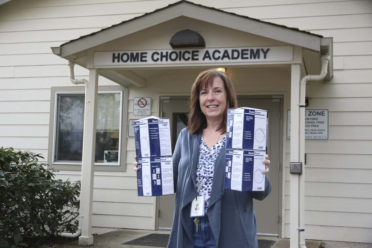 Janet Locasio, Program Coordinator, Home Choice Academy, holds boxes of masks to be donated to Clark County hospitals. Photo courtesy Evergreen Public Schools