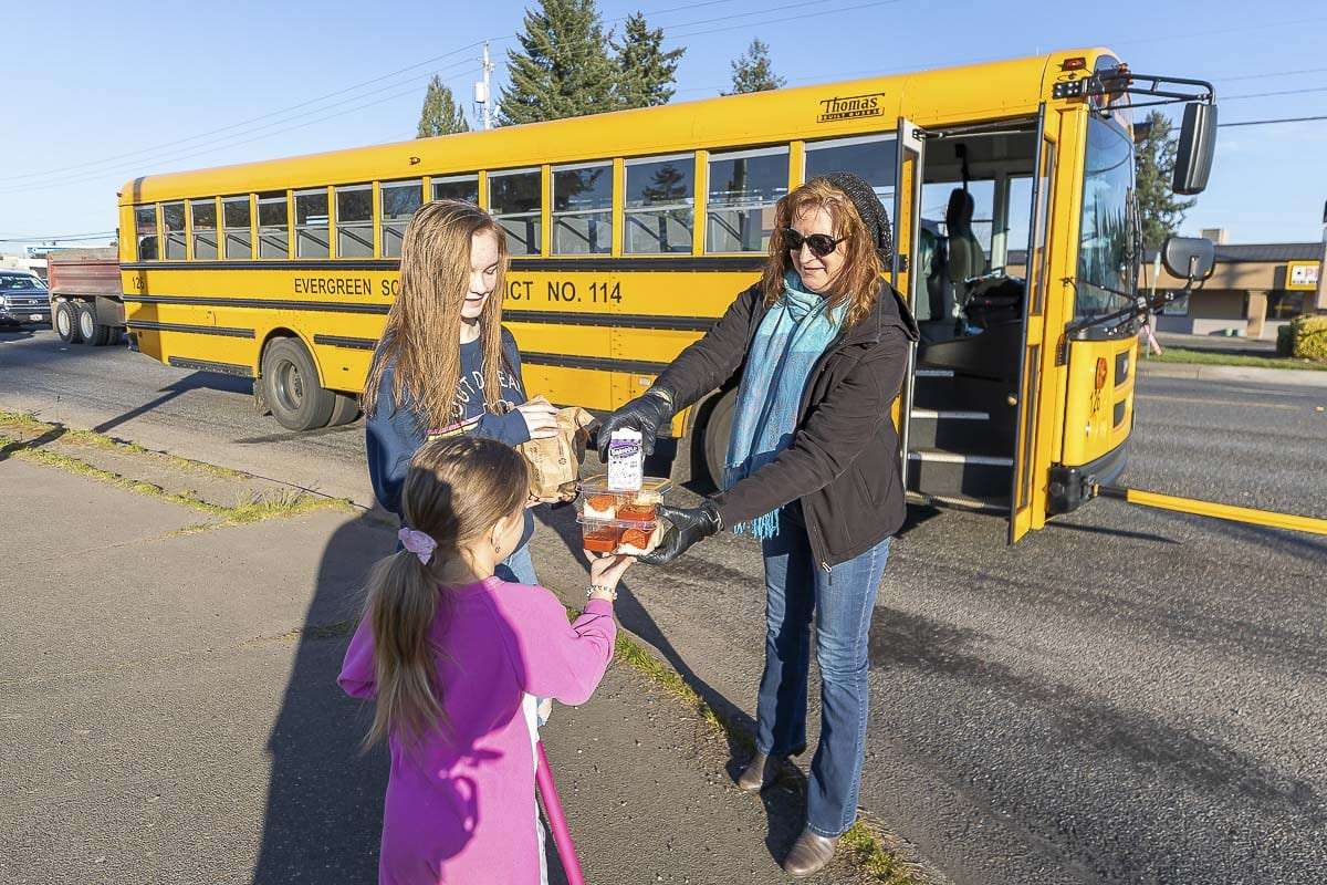 Kathy Young, a bus driver for Evergreen Public Schools, delivers a couple of meals to students along her route Tuesday. Photo by Mike Schultz