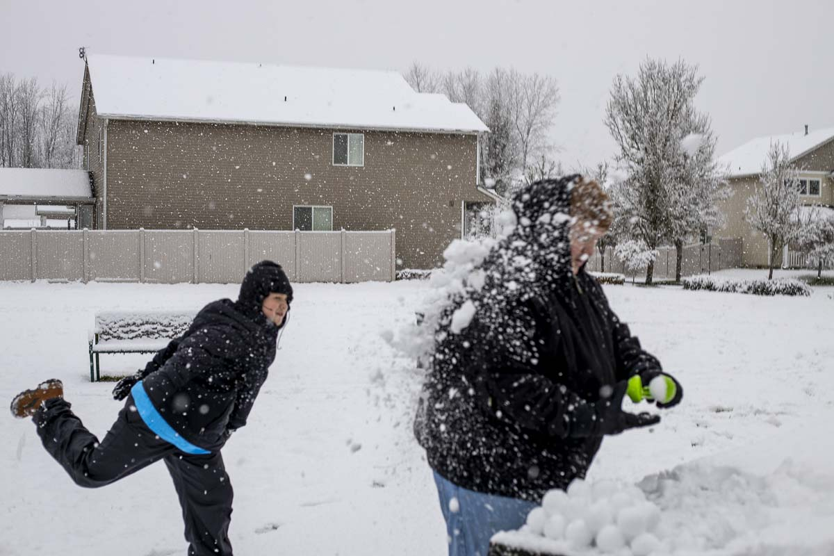 Wyatt Sanders of Battle Ground pelts his dad, Tarl, with a snowball on Saturday morning. Photo by Chris Brown