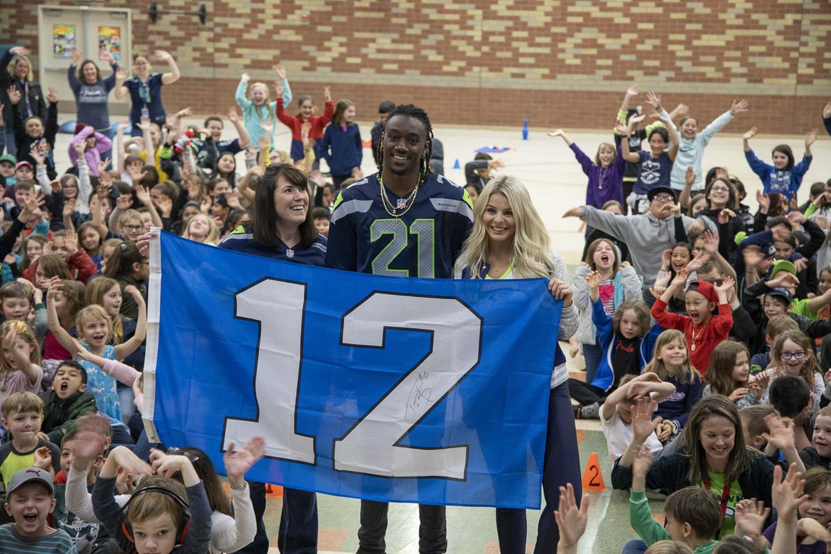 Seattle Seahawks cornerback Trey Flowers, Seahawks Dancer Kylie, and York Elementary School Principal Dawn Harris hold a 12th Man flag during assembly on Monday. Photo by Chris Brown