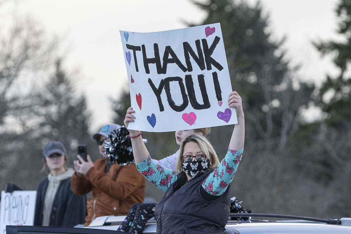 Christine Douglas of Washougal holds up a sign saying thanks to medical workers at PeaceHealth Southwest Medical Center in Vancouver on Wednesday night. Photo by Mike Schultz