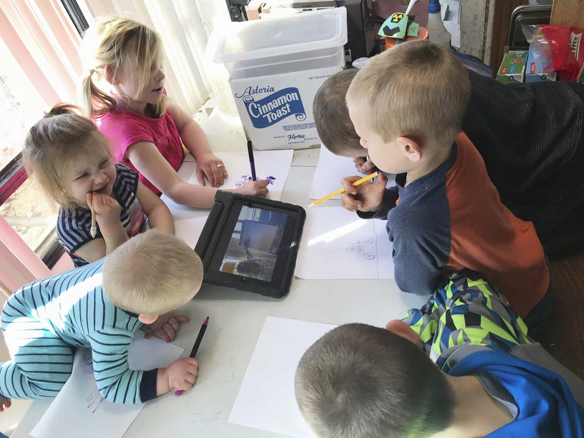 Six siblings huddle around a tablet while learning remotely. Photo courtesy of Battle Ground Public Schools
