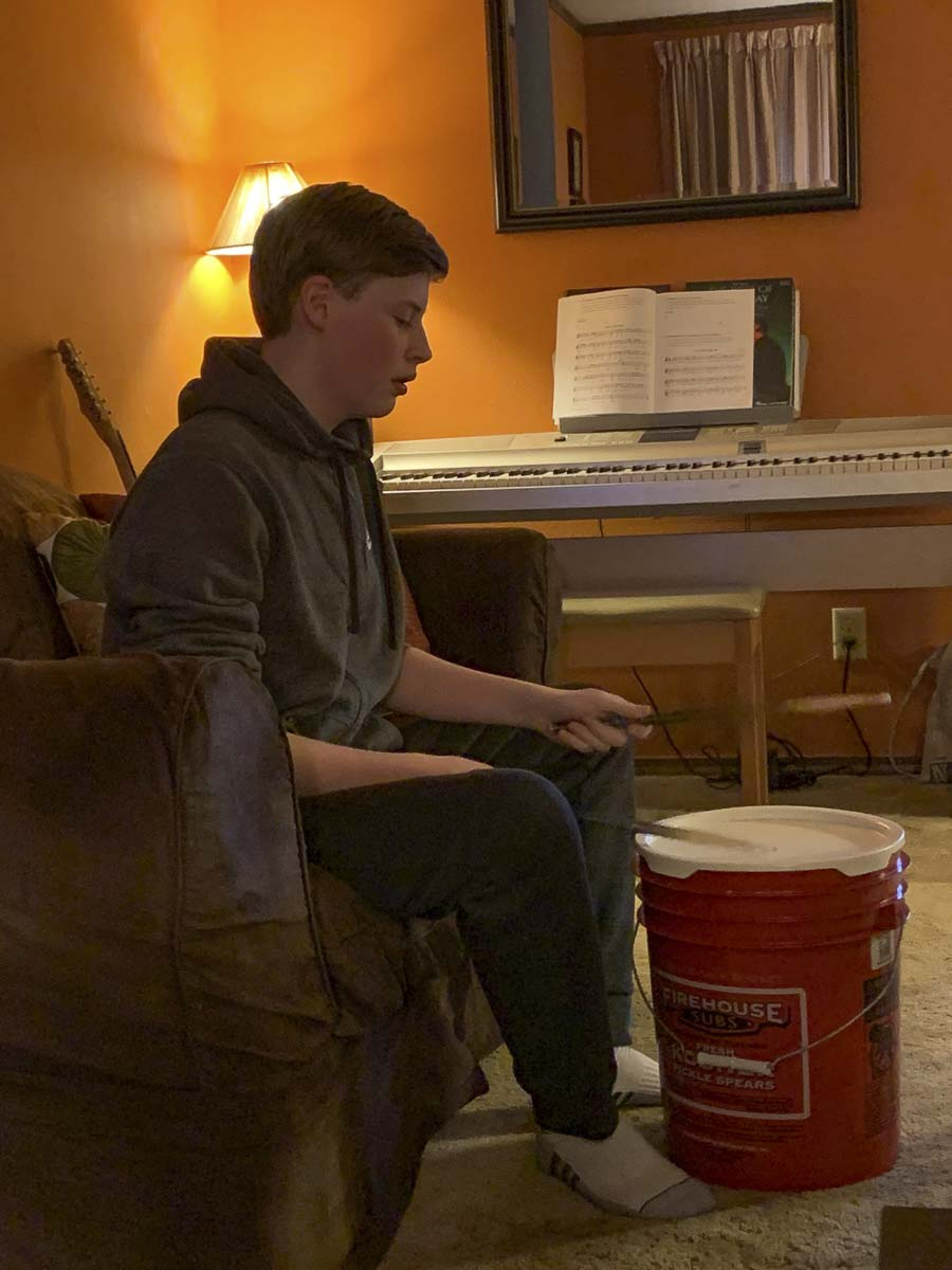 "Wyatt Baxter plays a five-gallon bucket as a drum for his ""Stomp"" class while on a Zoom call with his teacher and classmates across the area. Photo courtesy of Journey Theater"