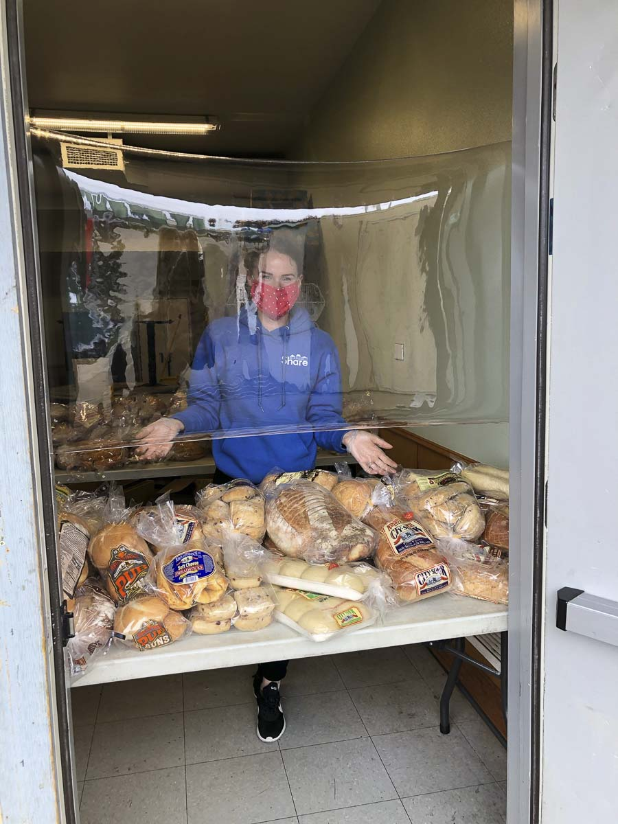 Bread loaves are given out to the homeless and those in need at the Share location in Vancouver. Clear Plastic shields protect servers and customers. Photo courtesy of Share Vancouver