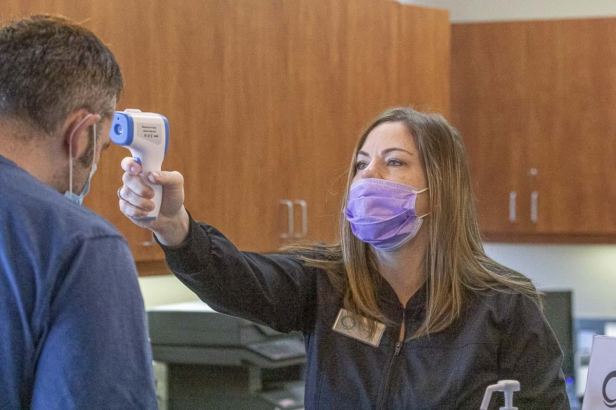 At the Smiles Dental office in Camas, front desk administrator Jena Ewald is seen checking patient Dan Stoica's temperature prior to his appointment. Photo by Mike Schultz