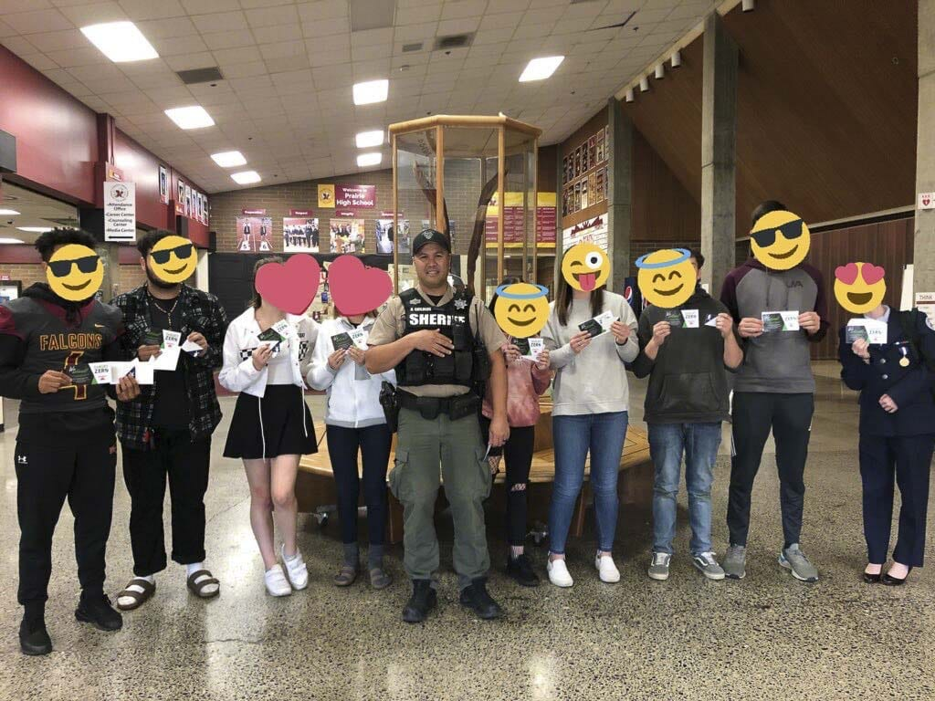 Students at Prairie High School stand with their school resource officer, Deputy Childers, back in November. Each received a gift card for driving safely. Photo courtesy of Target Zero