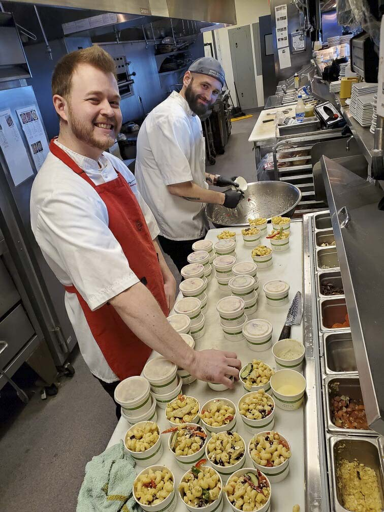 "Twigs Bistro Executive Chef and Sous Chef, Spencer Spencer (back) Galbraith and Teagan Moore (front) prepare meals for donation to area hospitals as part of the ""Buy a Meal, Give a Meal"" program. Photo courtesy of Twigs Bistro"
