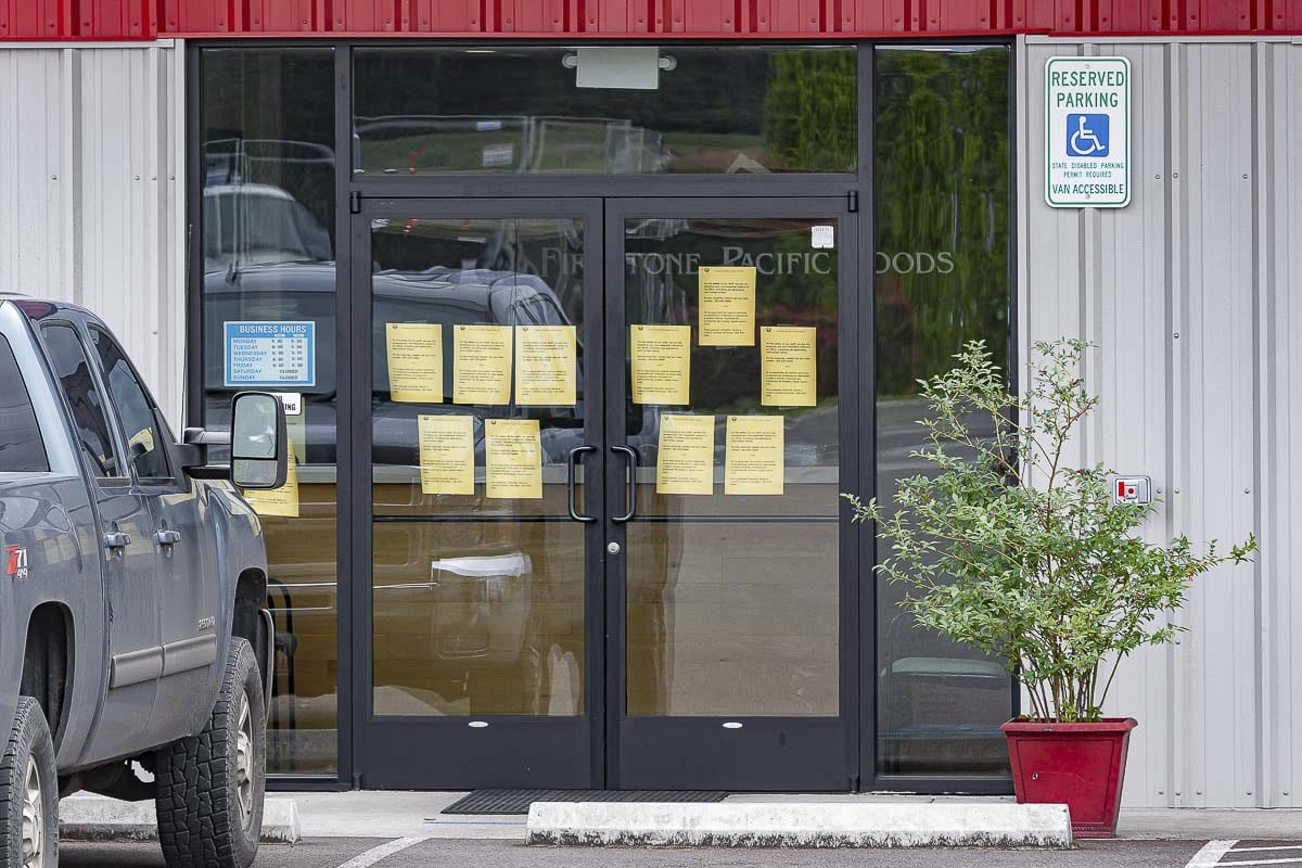 Notices posted by Clark County Public Health about a COVID-19 outbreak are taped to the main entry at Firestone Pacific Foods in Vancouver. Photo by Mike Schultz