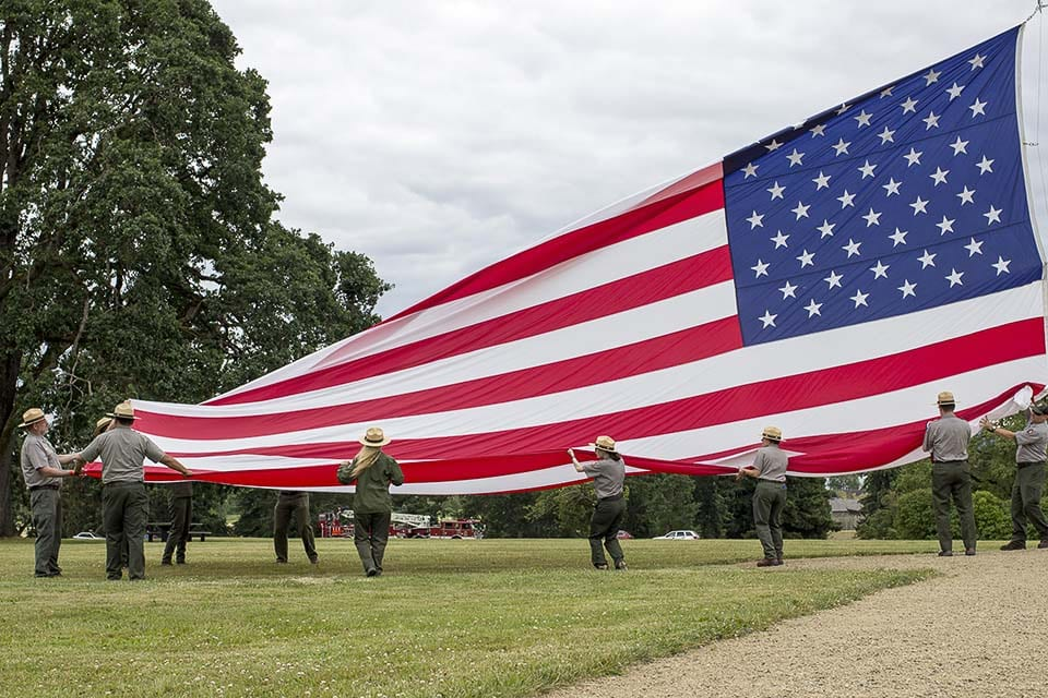 National park rangers raise the large garrison flag on the Vancouver Barracks Parade Ground on Flag Day, 2018. Photo courtesy of National Park Service/Junelle Lawry