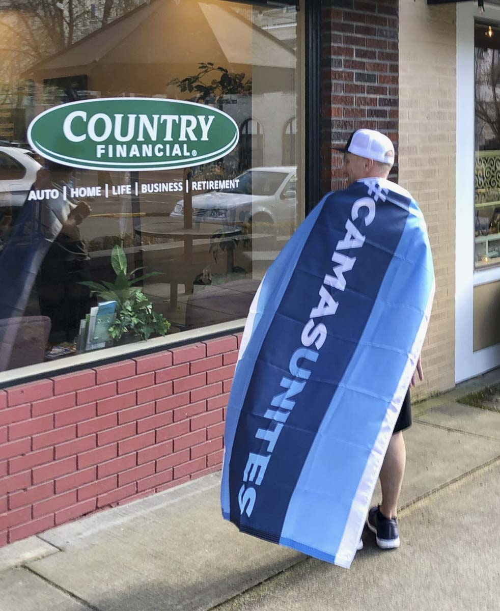 """Kris Cavin sports his Camas Unites """"cape"""" in front of his business in downtown Camas. KC Fresh has become a superhero of sorts with his dedication to students at Camas High School and beyond. Photo courtesy Kris Cavin"""
