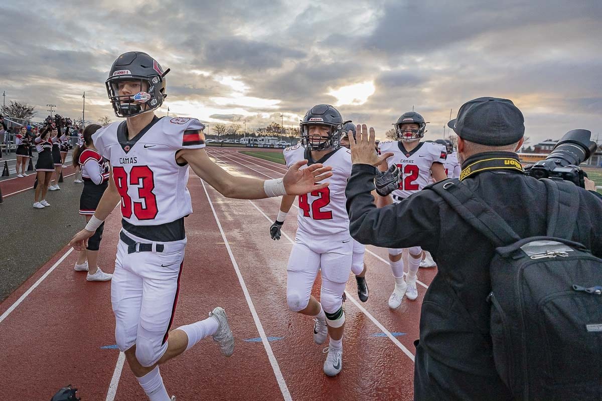 Camas football players give photography enthusiast Kris Cavin high-fives prior to the Class 4A state championship football game in December. KC Fresh, as he is known, has taken photographs of students for years. Photo by Mike Schultz