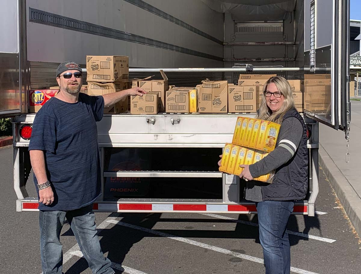 Shawn Fenmore, a driver with Landstar Ranger Trucking, drove 25 cases of unwanted cookies and crackers up to Woodland after his last stop in Vancouver to say thanks for Woodland Public Schools opening the high school as a temporary rest area for drivers. Photo courtesy of Woodland Public Schools