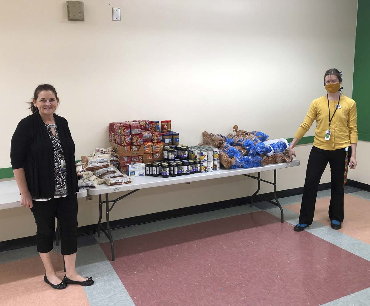 """Stacy Brown, business manager for Woodland Public Schools, and Gabrielle """"Gabby"""" Meador stand with assembled weekend food bags for families in need thanks to the $3,500 donation from Fibre Federal Credit Union. Photo courtesy of Woodland Public Schools"""
