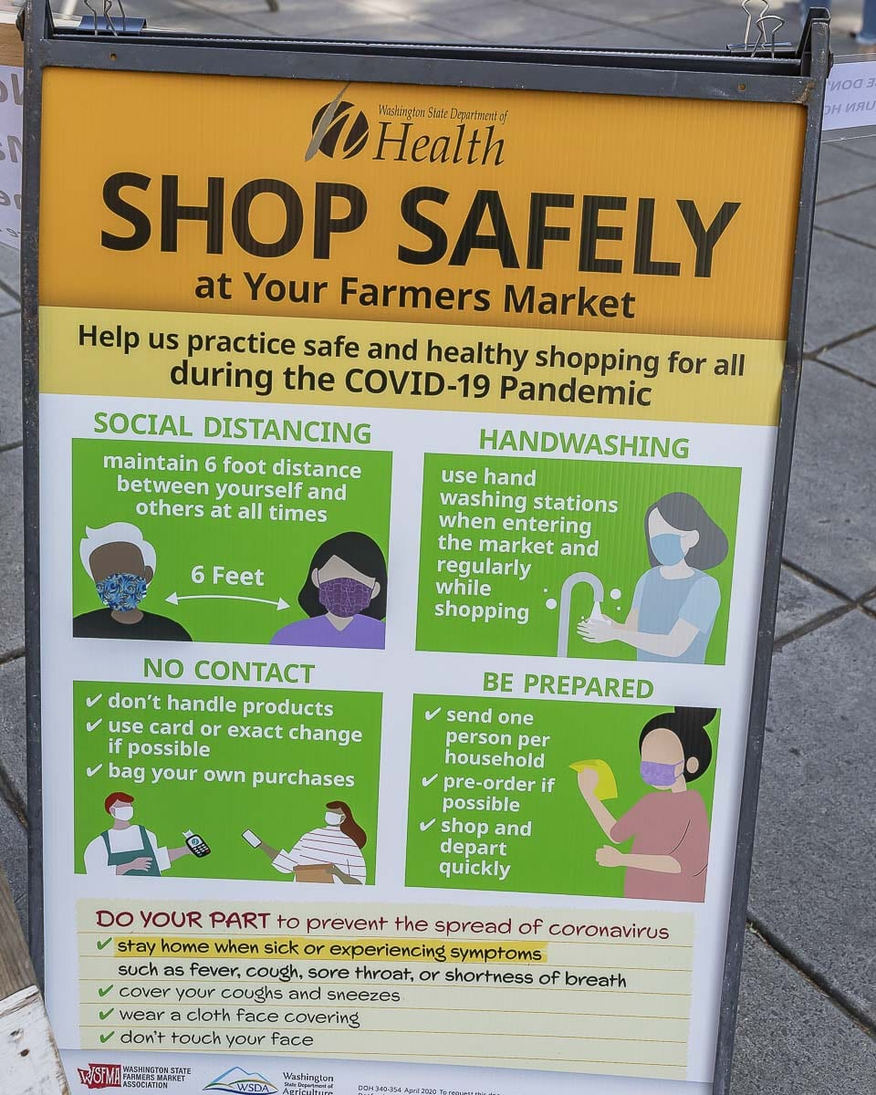 Signage like what is shown here, has been placed around and throughout the market to remind shoppers to social distance and if possible, wear masks. Photo by Mike Schultz