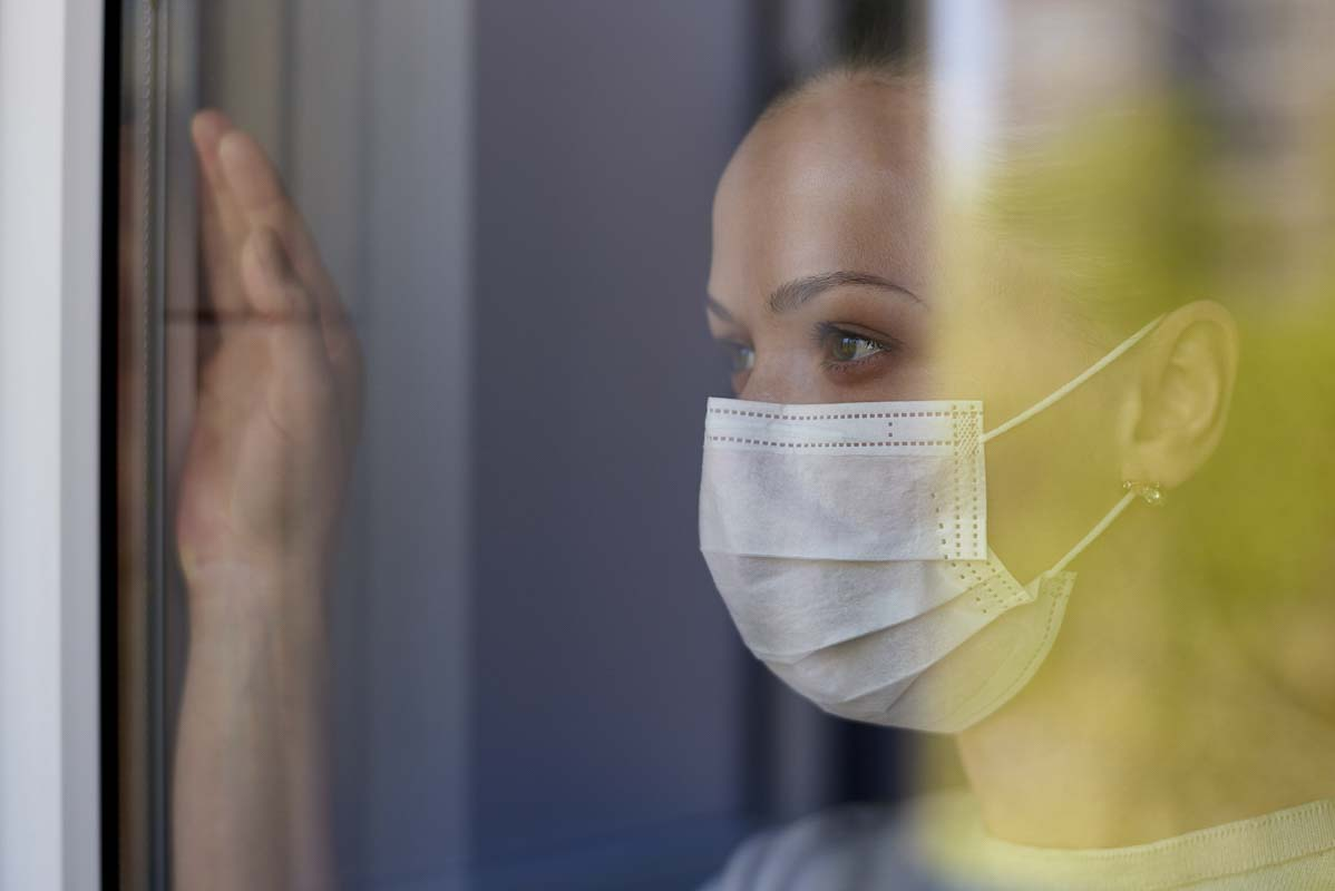 An unidentified woman looks out the window while wearing a mask. Stock Photo