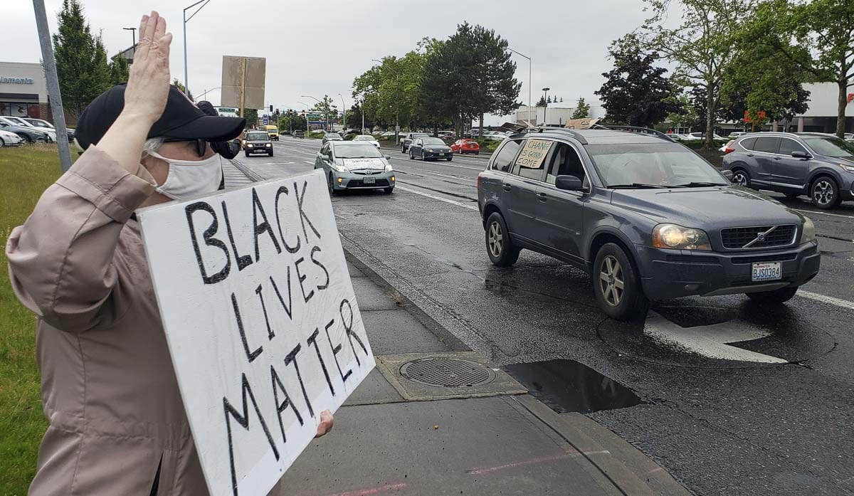 Geni Donaghey, who works at Crestline, holds up a Black Lives Matter sign as a car with more signage passes by Friday night in Vancouver. Black Lives Matter and the Washington Education Association teamed up for a rally. Photo by Paul Valencia