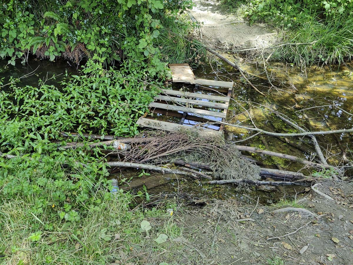 Pallets and other wood have been used to cross a seasonal creek in Cedar Trails Park in Battle Ground. Photo by Chris Brown