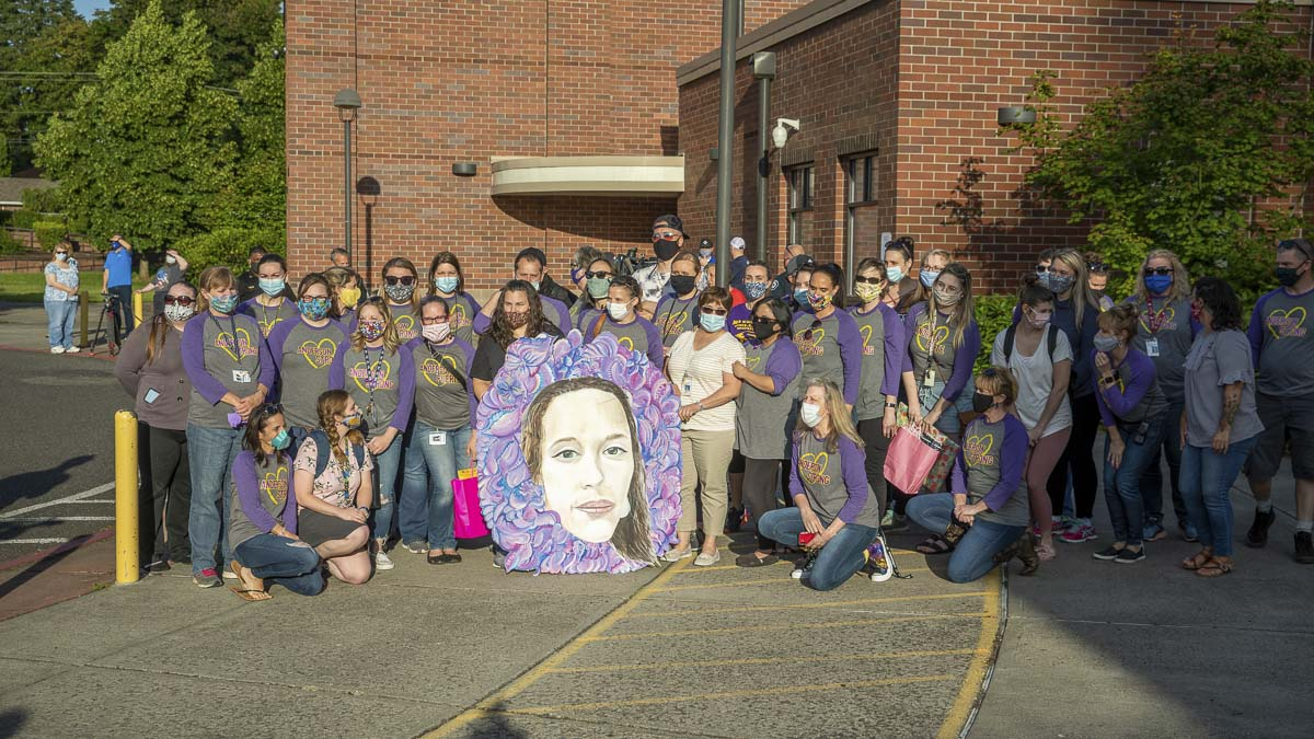 Staff and faculty of Sarah J. Anderson Elementary School pose for a photo with a memorial mural of Tiffany Hill. Photo by Jacob Granneman
