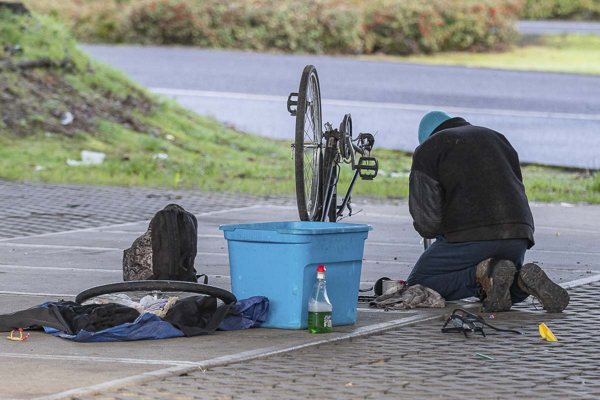 A homeless man works to fix a bicycle underneath the SR-14 overpass at Columbia Way in Vancouver during the Point in Time count on Jan. 30, 2020. Photo by Mike Schultz