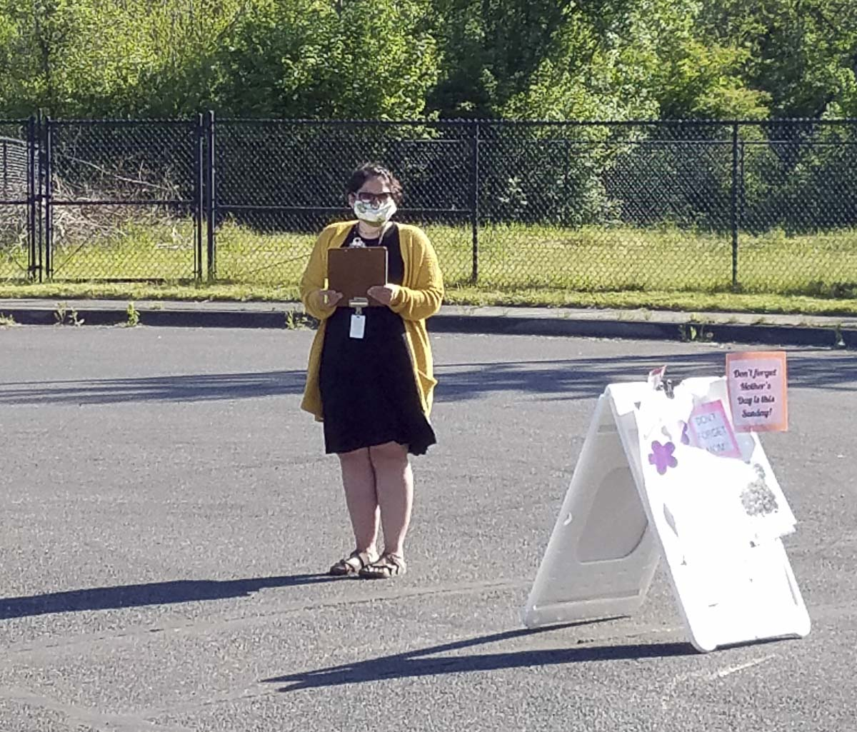 Nearly two dozen district employees helped make the plant sale happen like Stacy Gould pictured here wearing a mask while she checked in customers. Photo courtesy of Woodland Public Schools
