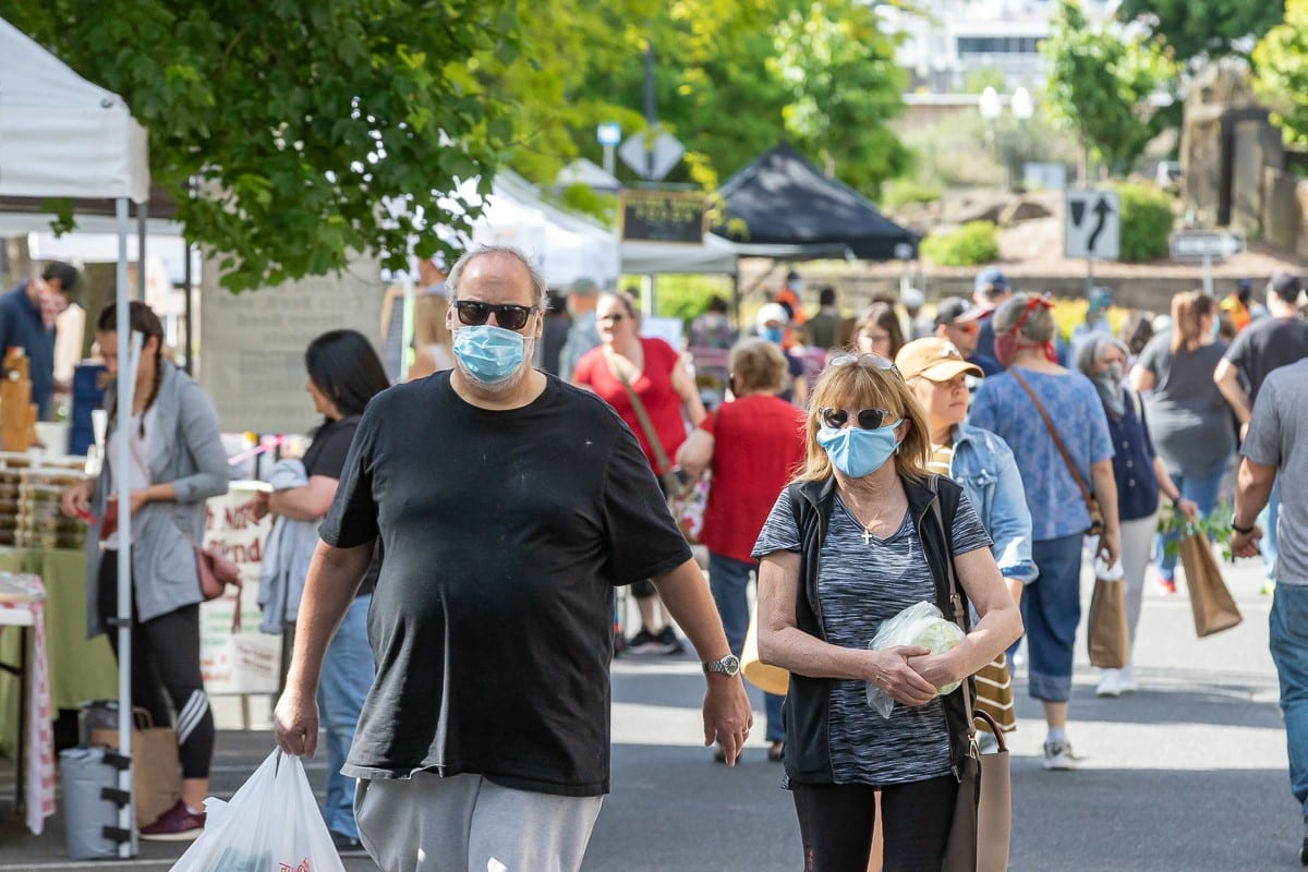These recent visitors to the Vancouver Farmers Market donned face masks but not all Clark County residents are thrilled with the governor's new requirements. Photo by Mike Schultz