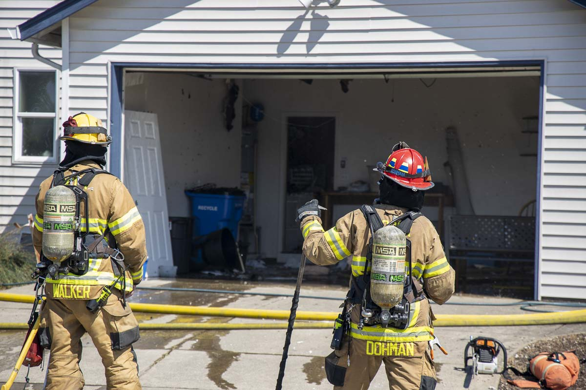 Firefighters with Clark County Fire District 3 wait to go back into a burning home in Battle Ground on Monday. Photo by Chris Brown