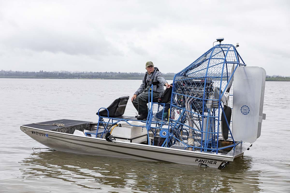 Terry McNabb is shown here Tuesday applying a treatment to address a milfoil infestation at Vancouver Lake. Photo by Mike Schultz