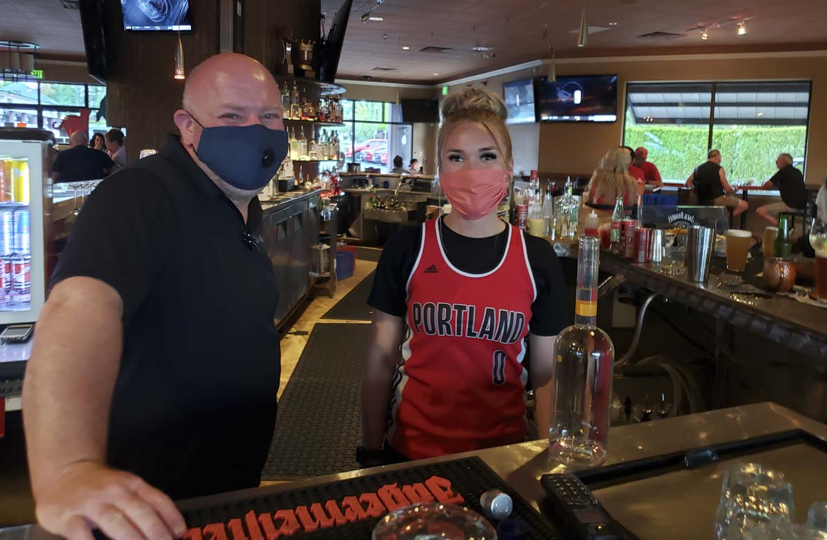 Jason Pinney, left, is the general manager, and Jessi Toombs, bartender extraordinaire, are ready to serve you at Main Event Sports Grill in east Vancouver. The restaurant business is trying to cope with pandemic rules. Sports-themed restaurants are grateful that sports are back. Photo by Paul Valencia