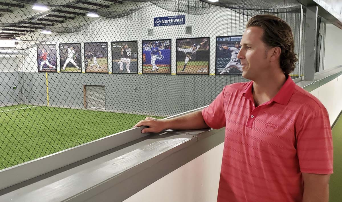 Nik Lubisich, a Vancouver-based sports agent, owns Northwest Sports Management Group. Here he is overlooking his indoor baseball training facility, Northwest Athletic Center, in east Vancouver. Behind him are photos of his Northwest clients who have made the big leagues, including Camas' Taylor Williams and Skyview's Ian Hamilton. Photo by Paul Valencia